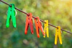 Gekleurde wasknijpers op een kabel op een achtergrond van groene bomen binnen Royalty-vrije Stock Foto's