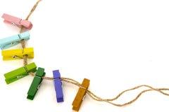 Gekleurde wasknijpers op een kabel op wit Stock Fotografie