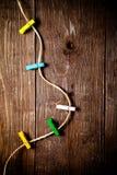 Gekleurde wasknijpers op kabel op een houten lijst of raad voor backg Stock Afbeeldingen