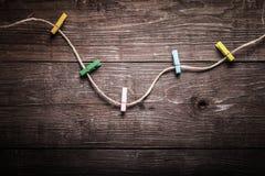 Gekleurde wasknijpers op kabel op een houten lijst of raad voor backg Royalty-vrije Stock Afbeeldingen