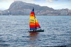 Gekleurde zeil hobbycat catamaran dicht bij de stad van Alicante Stock Afbeeldingen