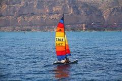 Gekleurde zeil hobbycat catamaran dicht bij de stad van Alicante Royalty-vrije Stock Afbeelding