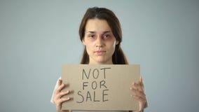 Gekneuste vrouwenholding niet voor verkoopteken, het menselijke handel drijven, seksuele aanval stock videobeelden