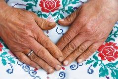 Geknitterte alte Hände und Handarbeit Lizenzfreies Stockfoto