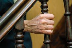 Geknitterte Hände der alten Frau halten das Geländer an Stockfotografie