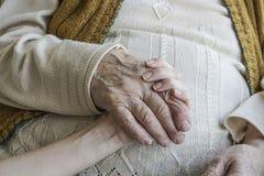 Geknitterte Hand, die eine jüngere Hand hält Lizenzfreies Stockfoto