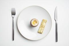 Gekochte Ei- und Toastsoldaten auf Platte mit Messer und Gabel Stockbild