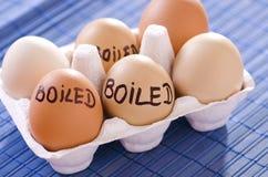 Gekochte Eier im Papiersatz auf dem Tisch Lizenzfreie Stockfotos