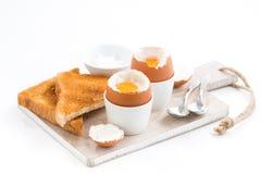 Gekochte Eier und knusperige Toast auf einem hölzernen Brett Lizenzfreie Stockfotografie