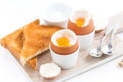 Gekochte Eier und knusperige Toast auf einem hölzernen Brett, Nahaufnahme Stockfoto