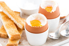 Gekochte Eier und Toast auf hölzernem Brett, Nahaufnahme, selektiver Fokus Lizenzfreies Stockbild