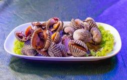 Gekochte Herzmuscheln auf weißer Platte mit Gemüse lizenzfreie stockfotografie
