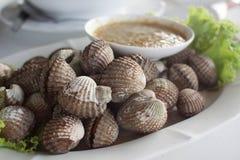 Gekochte Herzmuscheln oder Kamm-Muschel mit Meeresfrüchtesoße Lizenzfreie Stockfotografie