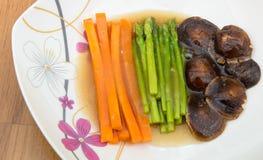 Gekochte Karotte, Shiitakepilz und Spargel mit brauner Soße Lizenzfreies Stockbild