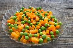 Gekochte Karotten mit grünen Erbsen Stockfotografie