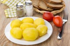 Gekochte Kartoffeln in der Platte, in den Gewürzen, in den Tomaten, im Brot und in der Gabel Lizenzfreie Stockfotos