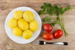 Gekochte Kartoffeln in der Platte, in der Petersilie, in den Tomaten und in der Gabel auf Tabelle Lizenzfreies Stockbild