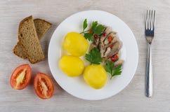 Gekochte Kartoffeln mit Heringen in der Platte, im Brot, in den Tomaten und in der Gabel Stockfotografie