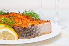 Gekochte Lachse bedeckt mit Karotten und Dill mit Zitronenstücken Stockbilder