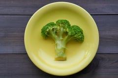 Gekochter Brokkoli auf einer gelben Platte Lizenzfreie Stockfotos