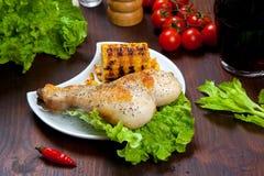 Gekochter Hühnerschenkel mit einer Grenze des Maiskolbens und des Salats Stockbilder