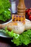 Gekochter Hühnerschenkel mit einer Grenze des Maiskolbens und des Salats Lizenzfreies Stockbild