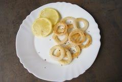 Gekochter Kalmar schellt mit Zitrone und Gewürzen auf weißem Teller Stockfotos