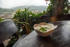Gekochter Reis mit Schweinefleisch, Pilz und Gewürzsuppe in einer weißen Schüssel auf Holztisch mit Bergblick und Garten Lizenzfreies Stockbild