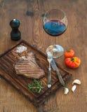 Gekochtes Steak des Fleischförmigen knochens auf Umhüllungsbrett mit Knoblauchzehen, Tomaten, Rosmarin, Gewürzen und Glas Rotwein Stockbild