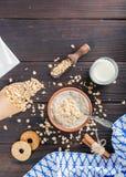 Gekookt havermoutpaphavermeel in een kom op houten donkere achtergrond Ingrediënten voor het koken stock afbeeldingen
