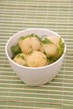 Gekookte aardappels met peterselie op een bamboe stock fotografie