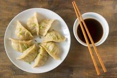Gekookte acht of gebraden die jiaozi of gedza met sojasaus wordt gediend stock afbeelding