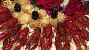 Gekookte die rivierkreeften en krabstokken met fruit op een dienblad wordt opgemaakt stock video