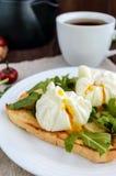 Gekookte eieren in een zak & x28; poached& x29; op toost en kernachtige groene bladeren van arugula en een kop thee royalty-vrije stock foto