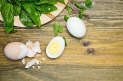 Gekookte eieren en Basilicumbladeren op houten achtergrond Stock Afbeelding
