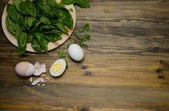 Gekookte eieren en Basilicumbladeren op houten achtergrond Royalty-vrije Stock Foto's
