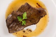 Gekookte kalfsvleeslever steack met saus op een witte plaat Stock Foto
