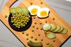 Gekookte kippeneieren, ingeblikte groene erwten en gesneden gemarineerde cucu Stock Afbeelding