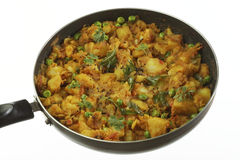 Gekookte kruidige aardappelvoorbereiding met andere groenten zoals ui en groene erwten royalty-vrije stock afbeelding