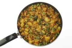 Gekookte kruidige aardappelvoorbereiding met andere groenten zoals ui en groene erwten royalty-vrije stock foto's