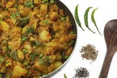 Gekookte kruidige aardappelvoorbereiding met andere groenten zoals ui en groene erwten stock afbeeldingen