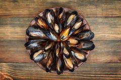 Gekookte mosselen in een kleischotel op hout Royalty-vrije Stock Afbeeldingen