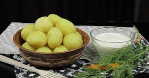 Gekookte nieuwe heerlijke aardappel op plaat op lijst klaar te eten Dille, zure room stock footage