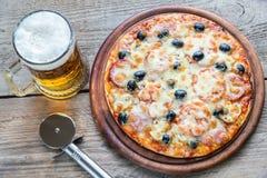 Gekookte pizza met een glas bier Stock Foto's