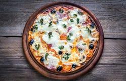 Gekookte pizza op de houten raad Stock Afbeeldingen