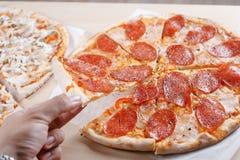 Gekookte pizza op dunne korst in de keuken Royalty-vrije Stock Afbeeldingen