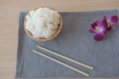 Gekookte rijst in een houten kom en eetstokjes op een houten achtergrond Royalty-vrije Stock Foto's