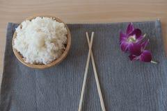 Gekookte rijst in een houten kom en eetstokjes op een houten achtergrond Stock Afbeeldingen