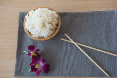 Gekookte rijst in een houten kom en eetstokjes op een houten achtergrond Royalty-vrije Stock Foto