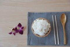 Gekookte rijst in een houten kom en lepel, eetstokjes op een houten achtergrond Royalty-vrije Stock Afbeeldingen